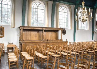Kerkbank achter stoelen.