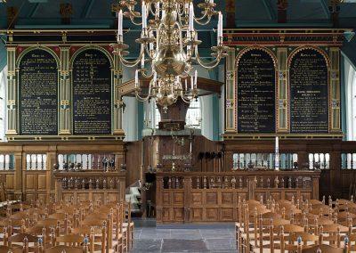 Zicht op interieur kerk door middenpad.