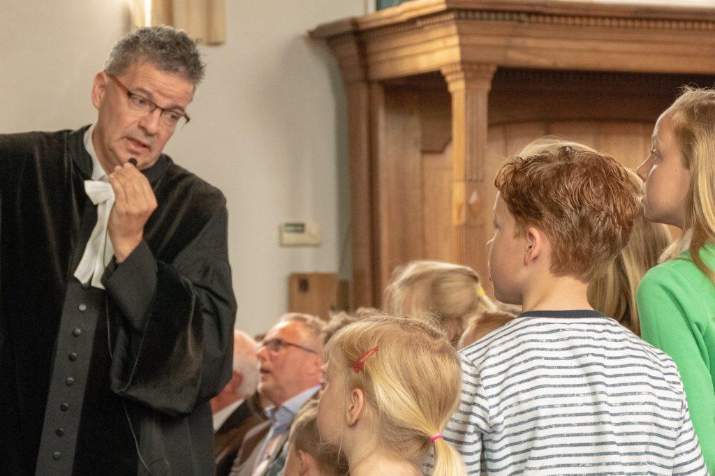 Dominee spreekt tegen kinderen tijdens kindermoment in kerkdienst.