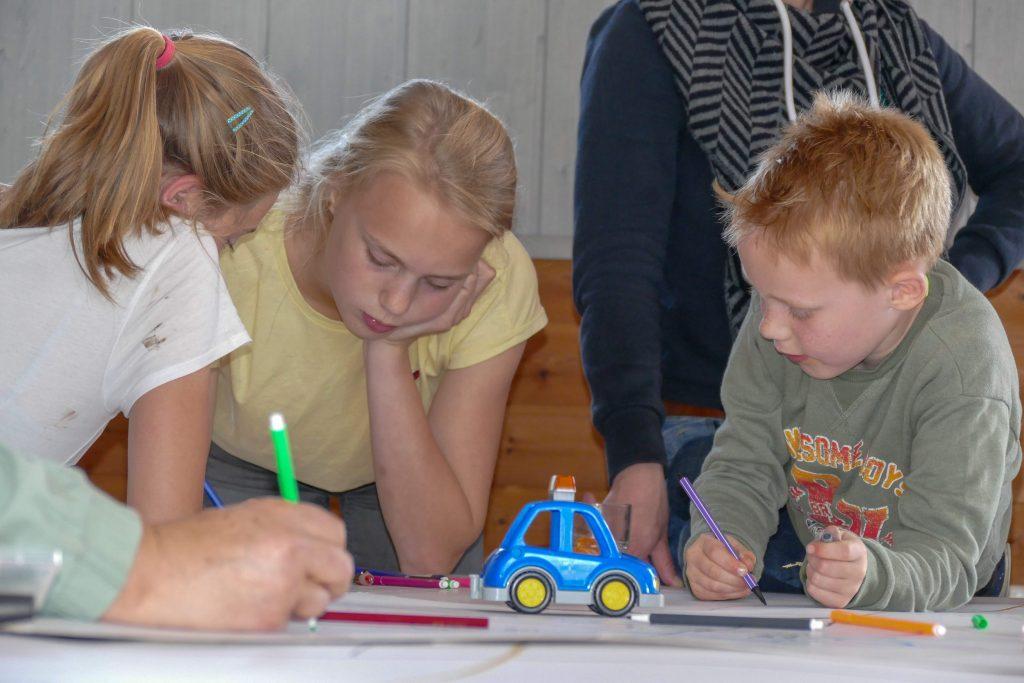 Kinderen tekenen op een groot vel papier op een tafel tijdens de Kinderkerk.
